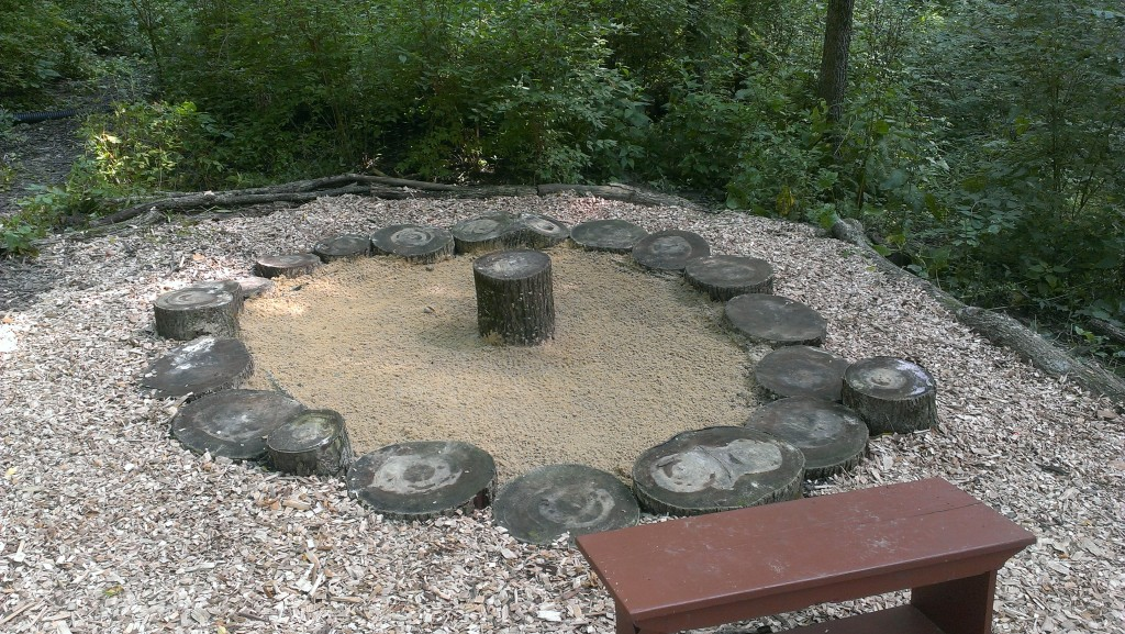 Sunken tree stumps create the border for this natural sand play area.